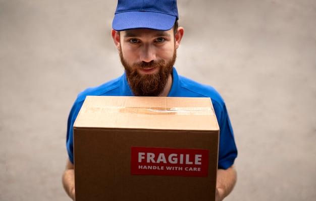 Gros plan sur un livreur avec une boîte fragile