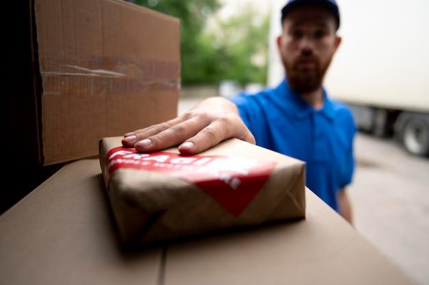 Gros plan livreur tenant la boîte