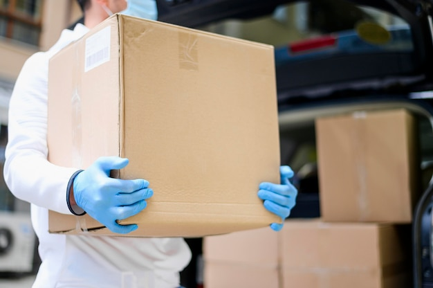 Gros plan livreur transportant une boîte en carton
