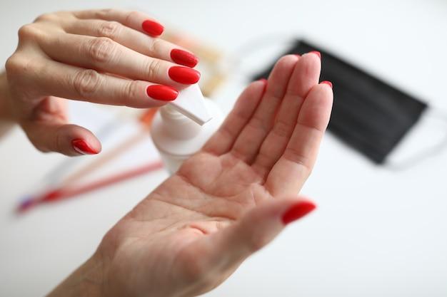 Gros plan de la lotion hydratante en appuyant sur les femmes à portée de main
