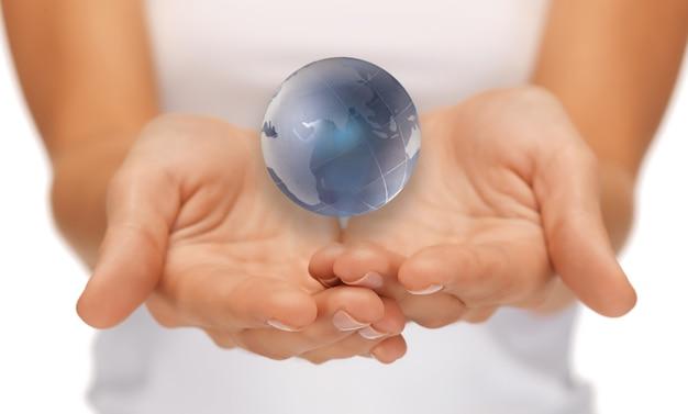 Gros plan lumineux photo de femme mains tenant le globe terrestre