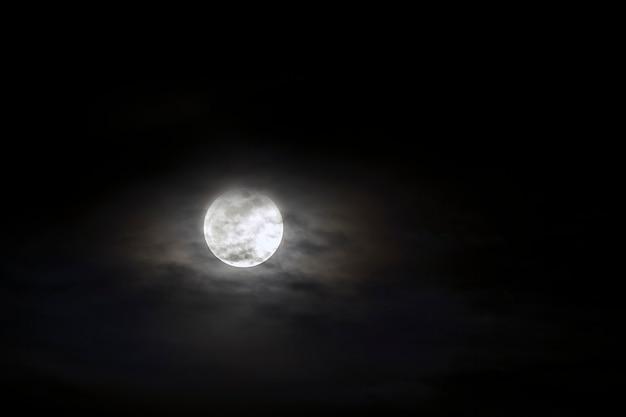 Gros plan de la lune rougeoyante argentée sur un ciel bleu foncé avec des nuages épars.