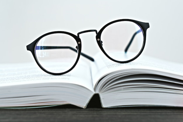 Gros plan de lunettes hipster pour lire sur un livre ouvert
