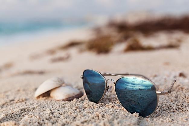 Gros plan de lunettes de soleil bleu sur la plage tropicale