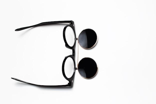 Gros plan de lunettes de soleil noires sur une surface blanche.