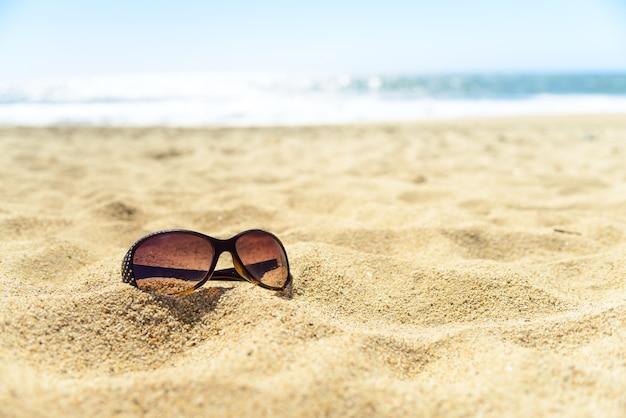Gros plan de lunettes de soleil sur la plage