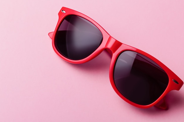 Gros plan de lunettes de soleil rouges élégantes sur fond rose