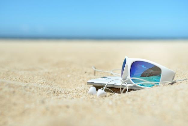 Gros plan de lunettes de soleil et de téléphone sur la plage