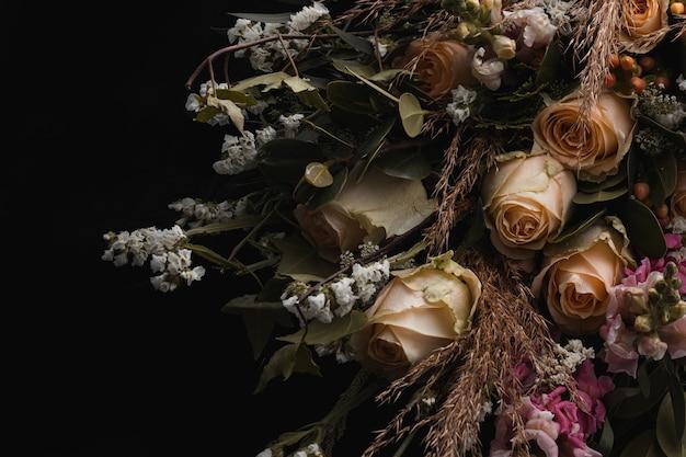 Gros plan d'un luxueux bouquet de roses orange et de fleurs blanches sur fond noir