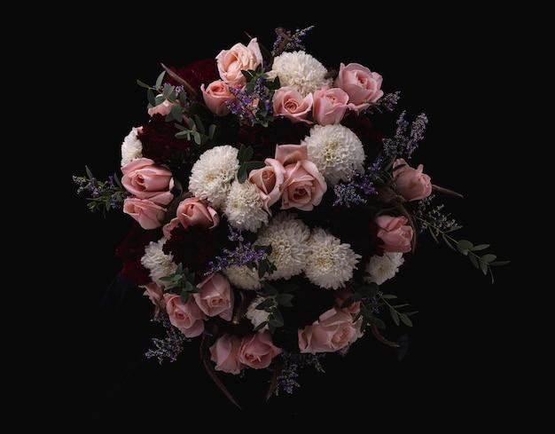 Gros plan d'un luxueux bouquet de roses roses et blancs, dahlias rouges sur fond noir
