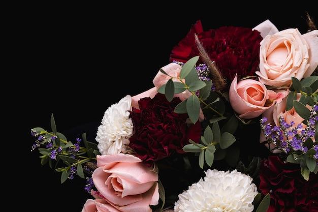 Gros plan d'un luxueux bouquet de roses roses et blancs, dahlias rouges