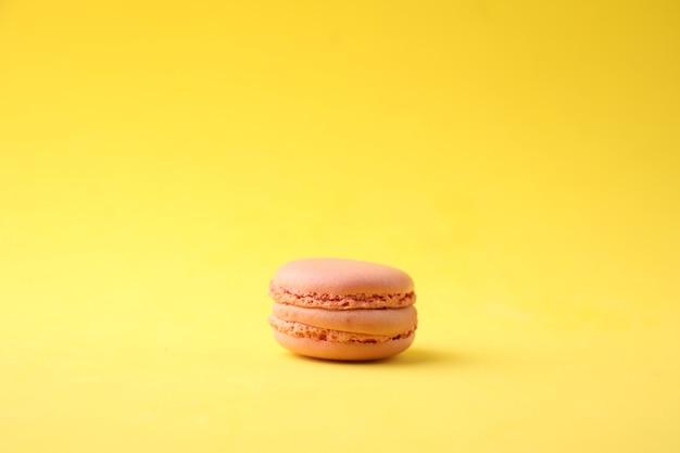 Gros plan d'un macaron rose sur fond jaune