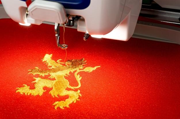 Gros plan de la machine à broder et le logo du lion d'or sur le tissu rouge