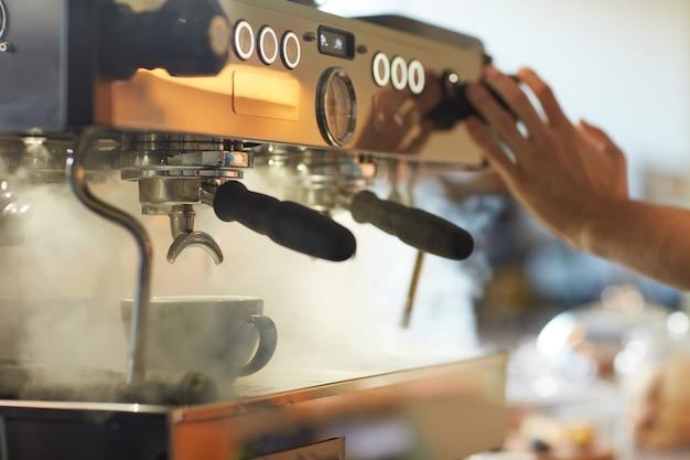 Gros plan sur une machine à café fumante dans un café ou un café avec des boutons de pression de barista méconnaissables, espace de copie