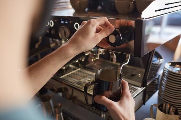 Gros plan sur une machine à café méconnaissable fonctionnant avec un barista tout en préparant du café frais dans un café ou un café, espace de copie