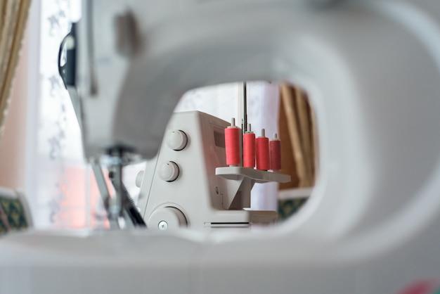 Gros plan d'une machine à coudre avec des bobines de fil de corail
