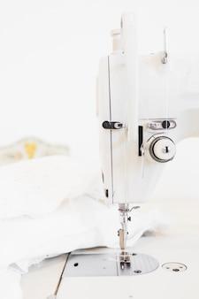 Gros plan de la machine à coudre et du tissu blanc