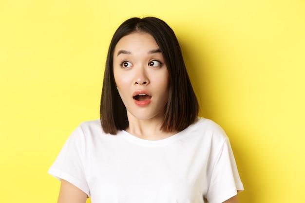 Gros plan de la mâchoire de baisse de fille asiatique surpris, haletant et regardant à gauche au logo, debout sur le jaune.