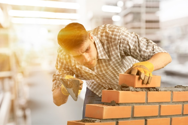 Gros plan sur un maçon industriel installant des briques sur un chantier de construction