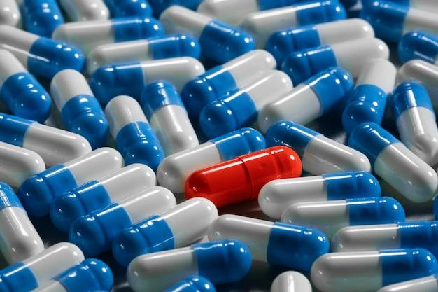 Gros plan macro d'une capsule rouge solitaire entourée de différents types de médicaments bleu-blanc. concept de solitude