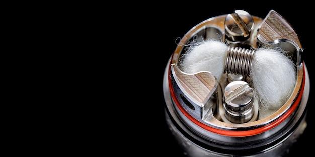 Gros plan, macro shot d'une seule micro-bobine avec une mèche de coton biologique japonais dans un atomiseur de réservoir d'égouttement reconstructible haut de gamme pour chasseur de saveurs, dispositif de vapotage, équipement de vape, vaporisateur