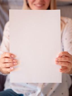 Gros plan d'un magazine-maquette tenu par une femme