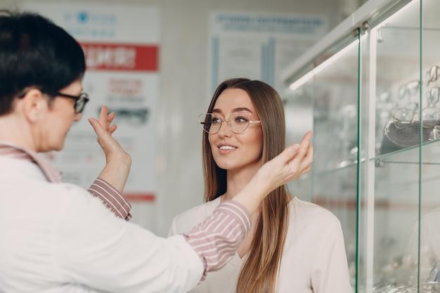Gros plan sur une magnifique jeune femme souriante souriante en train de ramasser et de choisir des lunettes au coin de l'opticien du centre commercial. heureuse belle femme achetant des lunettes de vue chez l'optométriste