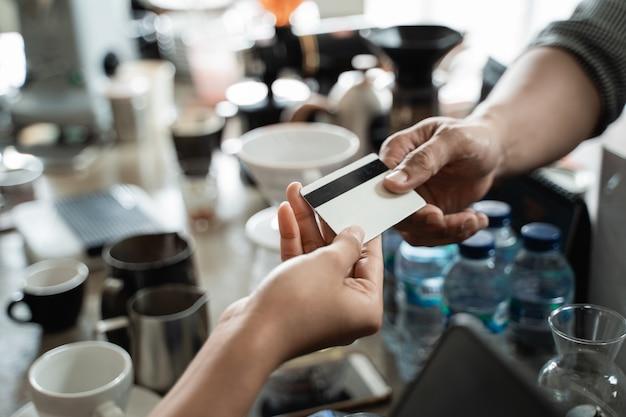 Gros plan de la main de l'acheteur donne une carte de crédit au vendeur