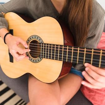 Gros plan d'une main d'adolescente jouant de la guitare