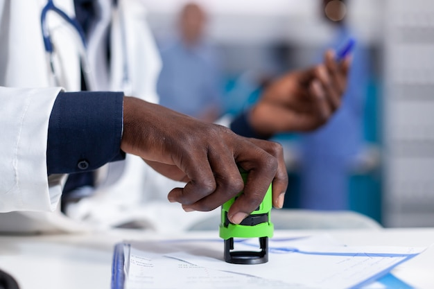 Gros plan d'une main afro-américaine tenant un timbre sur des papiers