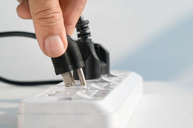 Gros plan d'une main âgée se branchant sur une prise électrique