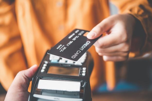 Gros plan sur la main à l'aide d'une carte de crédit pour payer en envoyant la carte de crédit au personnel de la machine de balayage de carte de crédit. paiement en ligne