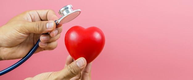 Gros plan sur la main à l'aide d'un stéthoscope pour vérifier le cœur.