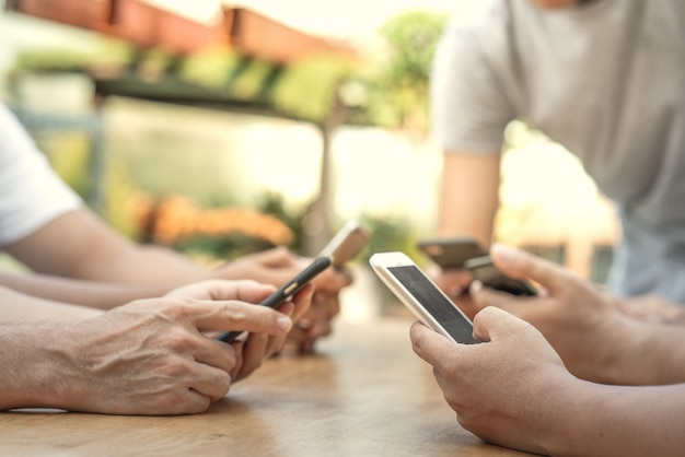 Gros plan la main à l'aide d'un téléphone intelligent mobile se connectant wifi internet en ligne à des gens du monde entier