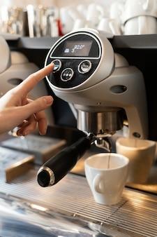 Gros plan main en appuyant sur le bouton de la machine