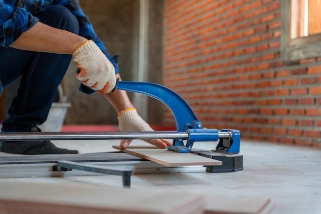 Gros plan sur la main d'un artisan carreleur sur un chantier de construction, un ouvrier coupe une grande dalle de carrelage lors de la construction d'une maison.