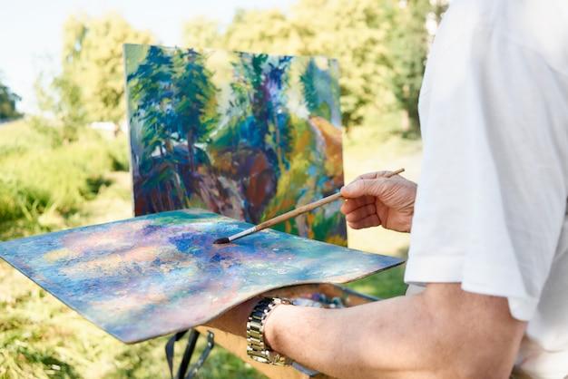 Gros plan d'une main d'artiste tenant un pinceau et une palette de couleurs contre un tableau presque terminé au parc.