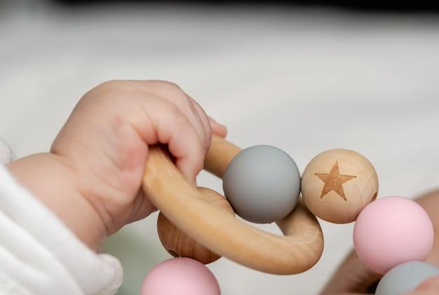 Gros plan d'une main de bébé, jouant avec un jouet en bois.