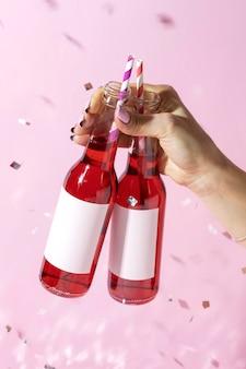 Gros plan de la main avec des bouteilles et des pailles