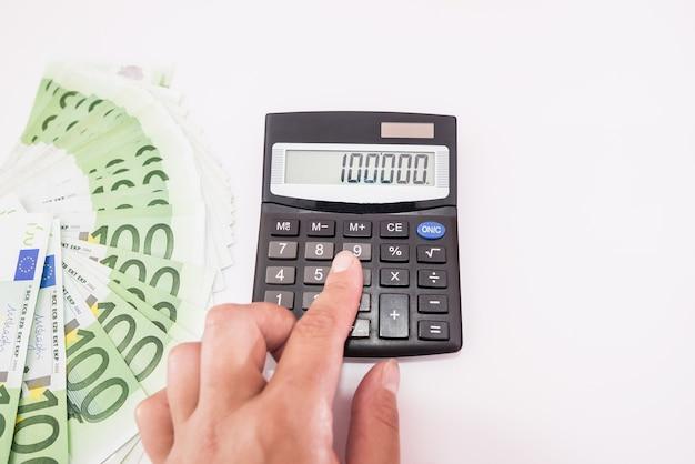Le gros plan d'une main calcule le revenu avec une calculatrice. notion financière. vue d'en-haut.
