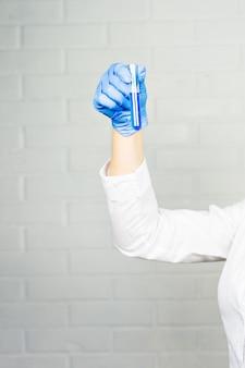 Gros plan sur la main d'une chercheuse médicale tenant un tube à essai avec un liquide bleu