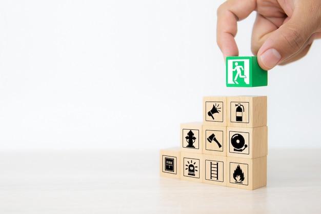 Gros plan main choisir des blocs de bois empilés avec l'icône de sortie de porte.