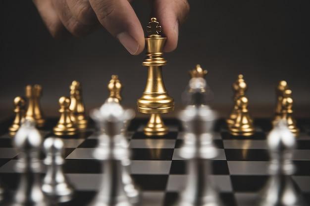 Gros plan main choisir les échecs d'or pour contester avec l'équipe d'échecs silve sur l'échiquier.