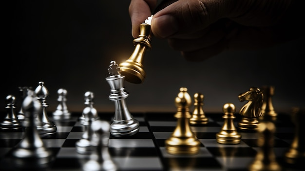 Gros plan main choisir les échecs d'or pour se battre avec l'équipe d'échecs d'argent sur l'échiquier