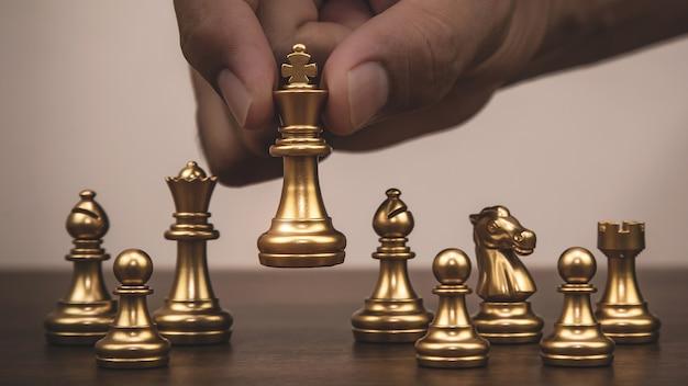 Gros plan main choisir le roi des échecs d'or