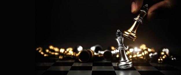 Gros plan main choisir le roi des échecs pour se battre sur l'échiquier.