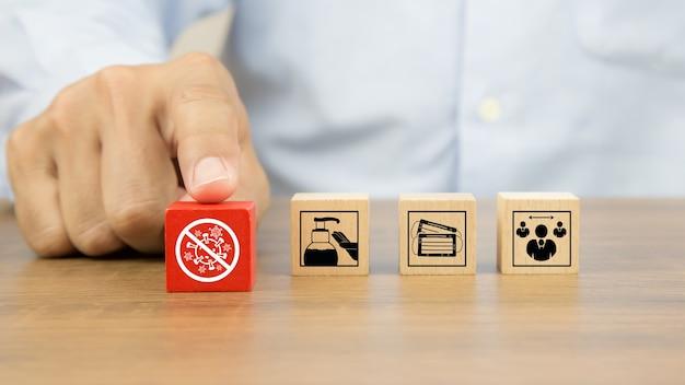 Gros plan main en choisissant l'icône de protection covid sur des blocs de jouets en bois