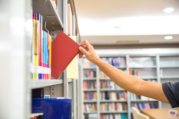 Gros plan de la main en choisissant un livre de la bibliothèque.