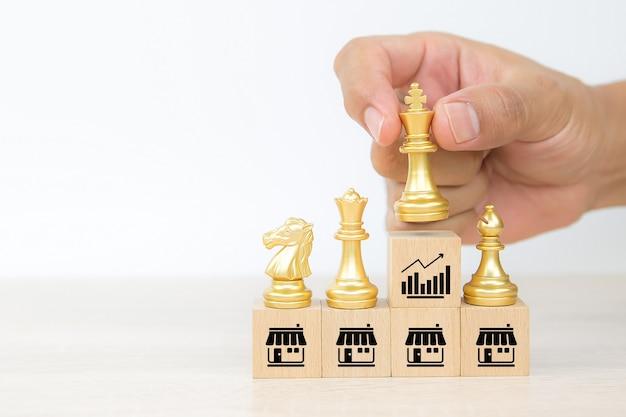 Gros plan sur la main, choisissez le roi des échecs sur un bloc de bois avec l'icône de la franchise.