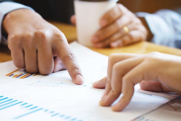 Gros plan d'une main de collègue d'affaires pointant sur le document commercial lors de la discussion à la réunion. réflexion des gens d'affaires au bureau.